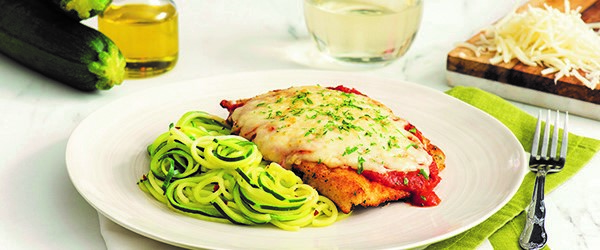 Photo of breaded chicken, topped with tomato sauce and melted cheese, served with a side of spiralized zucchini noodles.