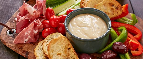 Photo of cheese dip on a board with cured meats, baguette pieces, cut vegetables and olives.