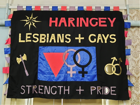 Image description: Photo of a colourful banner made of fabric. The banner has a black background and large letters,  reading 'HARINGEY LESBIANS AND GAYS, STRENGTH + PRIDE.'