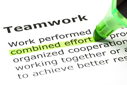 "Text on a page. The heading reads ""Teamwork"". The words ""combined effort"" are beeing coloured with a green highlighter pen."