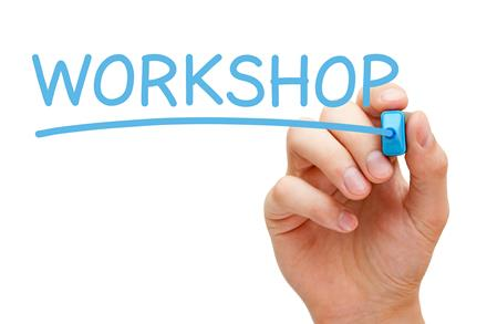 Hand holding a blue pen writing the word 'workshop'