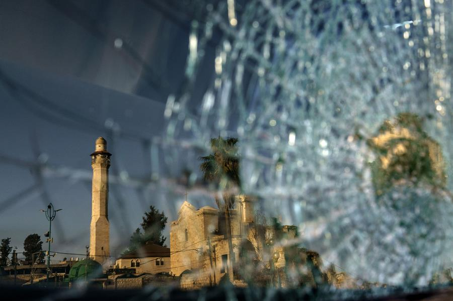 The minaret of the Al-Omari mosque and St. George Greek Orthodox church are reflected in the broken windshield of a vehicle sitting outside a synagogue in the mixed Arab-Jewish town of Lod, central Israel.