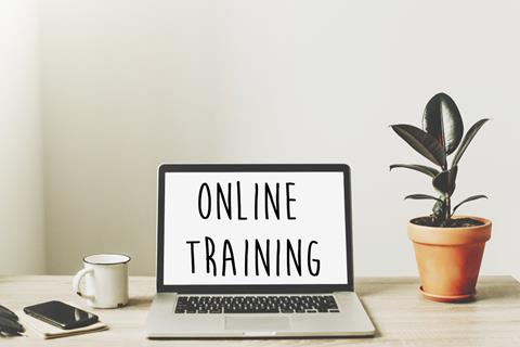 online training text on laptop screen on wooden desktop with phone, notebook, coffee and plant. business workspace. internet Education concept. e-learning