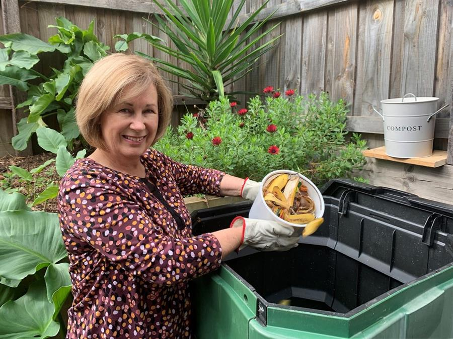 Person emptying food scraps into a compost bin in a garden