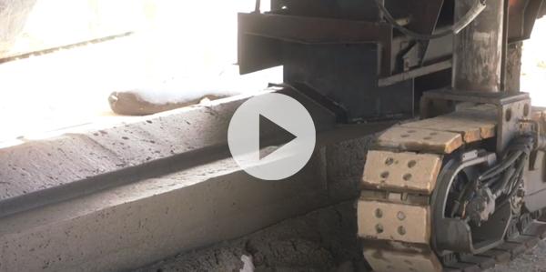 Slipform machine making a kerb from concrete.