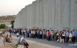 People queuing by the separation wall between Bethlehem and Israel