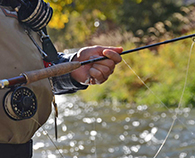 Keen angler with his freshwater fly rod and reel